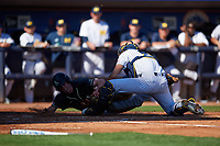 Michigan Wolverines catcher Harrison Salter (11) tags Jacob Hurtubise (39) out at the plate during a game against Army West Point on February 18, 2018 at Tradition Field in St. Lucie, Florida.  Michigan defeated Army 7-3.  (Mike Janes/Four Seam Images)