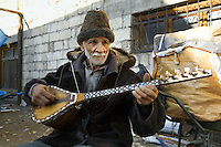 """Azerbaijan. Ganja region. Ganja. An old caucasian man with a hat and a white beard plays the """"saz"""", a plucked string instruments, popular in Azerbaijan, The saz is a long-necked lute of folk traditions and is descended from the kopuz; a generic name for several forms of stringed instrument used in Azeri music.  © 2007 Didier Ruef"""