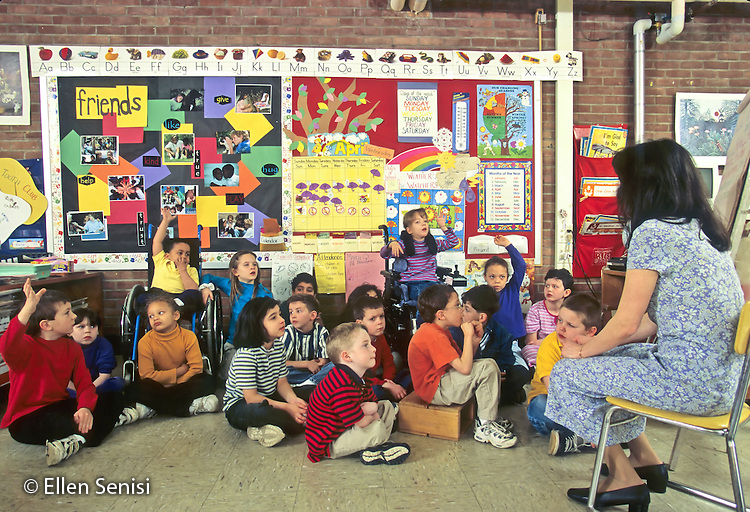 MR / Schenectady, New York. Zoller Public School / Grade 1 Inclusion classroom. Teacher with class group, some raising hands to participate. About one quarter of class includes mainstreamed special education students with mixed disabilities including learning disability, ADHD, spina bifida, scoliosis, and cerebral palsy. MR: MF © Ellen B. Senisi
