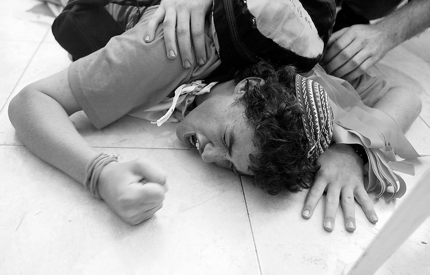 Youth screams while pounding hisw fist as he is sprawled out on the floor of the synagogue as Israeli soldiers gain entry in the Gaza Strip settlement of Katif this afternoon. Katif, Atzmona and Slav, the last three remaining communities in the main Gaza settlement bloc, Gush Katif, were evacuated with force today.  GUSH KATIF, GAZA STRIP  8/21/05