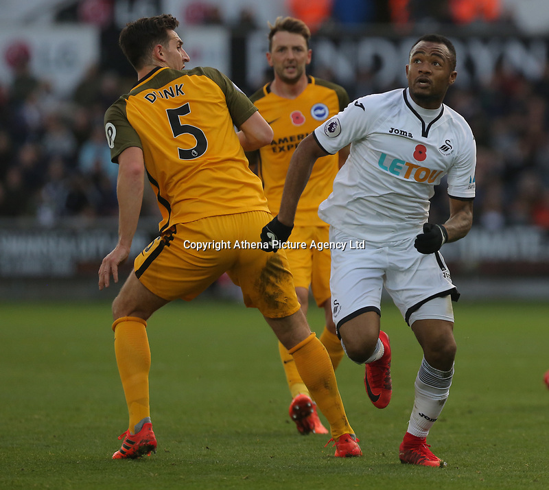 Jordan Ayew of Swansea City (R) looks up to the ball whie marked by Lewis Dunk of Brighton (L) during the Premier League match between Swansea City and Brighton and Hove Albion at The Liberty Stadium, Swansea, Wales, UK. Saturday 04 November 2017
