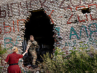 Natalia Voronkova, a volunteer who offers support and basic first aid training for Ukrainian government forces fighting Russian-backed separatists in the east of the country, visits a damaged former school building on the frontline.