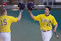 Michigan Wolverines outfielder Zach Zott (48) is greeted by teammate Kendall Patrick (15) during the NCAA season opening baseball game against the Texas State Bobcats on February 14, 2014 at Bobcat Ballpark in San Marcos, Texas. Texas State defeated Michigan 8-7 in 10 innings. (Andrew Woolley/Four Seam Images)