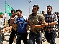 """Palestinians carrying an injuerd man during  Hamas demonstration in the Karni crossing east of Gaza City that injured 10 people and killing people by the Israeli army on May 22, 2008""""photo by Fady Adwan"""""""