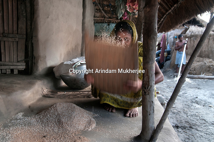 A woman separating husk powder from rice at her home in Sunderbans, West Bengal, India. Arindam Mukherjee