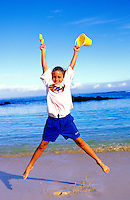 Young girl jumping and having fun at the beach.