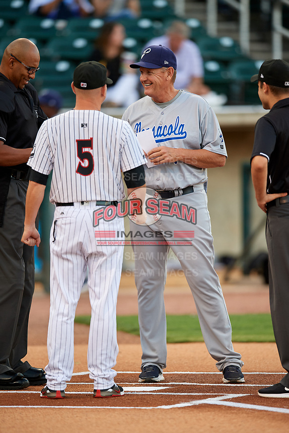 Pensacola Blue Wahoos manager Jody Davis (7) meets with Birmingham Barons manager Ryan Newman (5) and umpires Jose Navas, Alex Mackay and Reid Joyner (not pictured) at home plate before a game against the Birmingham Barons on May 8, 2018 at Regions Field in Birmingham, Alabama.  Birmingham defeated Pensacola 5-2.  (Mike Janes/Four Seam Images)