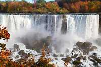 View of American Niagara Falls and rocks with beautiful red, yellow, green, and orange autumn foliage in Ontario Canada