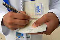 Milano - Rho Fiera 1/6/2015<br /> Il passaporto dell'Expo, uno dei gadgets più richiesti dai visitatori. Nella foto, all'entrata del padiglione degli Emirati Arabi, un membro dello staff pone il visto sul passaporto come ad una reale frontiera.<br /> The Expo passport, one of the gadgets most requested by visitors. In the photo, the entrance to the pavilion of Arab Emirates, a staff member puts the visa in the passport as at a real border.<br /> Foto Livio Senigalliesi