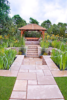 Sunken patio outdoor room landscaping, stone steps, garden gazebo and bench with cushions, water feature garden with waterlilies, lush flowers in green and gold and yellow color theme, wall fence, levels, home garden, stone path, walkway leading to building, blue skies and clouds, sunny day with blue sky