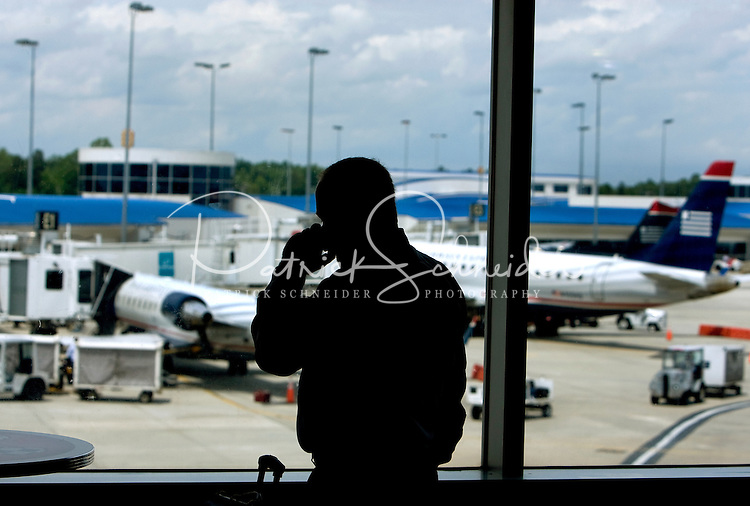 A passenger talks on the phone while waiting for his flight at Charlotte-Douglas International Airport. ..Charlotte-Douglas International Airport, one of US Airways' largest hubs, serves 10 major airlines, including Air Canada, Air Tran, American, Continental, Delta, JetBlue, Lufthansa, Northwest and United. The airport is the nation?s 10th largest in terms of total operations, the 18th largest in terms of total passengers and the 37th largest in terms of cargo. Charlotte-Douglas serves 640 daily flights, including direct flights to 120 cities. ..Photographer has series of images from Charlotte-Douglas International Airport, including aerials. ... PATRICK SCHNEIDER PHOTO.COM