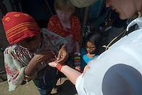 Kuna woman carefully tying beaded bracelet on wrist of visitor, Comarca De Kuna Yala, San Blas Islands, Panama