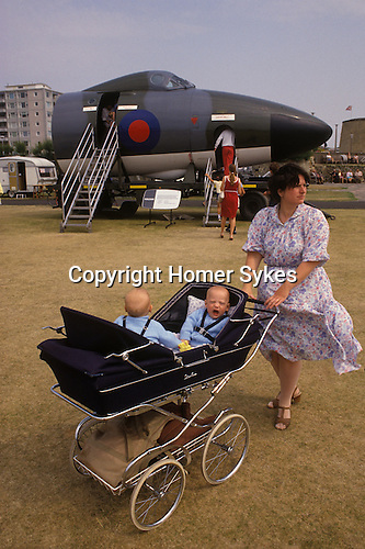 Bournemouth, Dorset. 1980's<br /> Dressed in baby boy blue, twins in their facing you, Silver Cross pram; yawn as their wind blown mother pushes her sons around an RAF display where half a Vulcan aircraft is on show.
