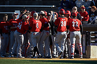 Patrick Price (30) of the Gardner-Webb Runnin' Bulldogs high fives teammates after scoring a run against the Wake Forest Demon Deacons at David F. Couch Ballpark on February 18, 2018 in  Winston-Salem, North Carolina. The Demon Deacons defeated the Runnin' Bulldogs 8-4 in game one of a double-header.  (Brian Westerholt/Four Seam Images)