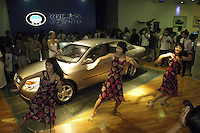 Chinese modles dance beside a BYD during the Auto China 2004 exhibition in Beijing, China. BYD Auto Co., Ltd., hold by Shenzhen BYD Company, is this country's largest private run passenger car manufacturer..