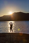 Woman in silhouette on Lake Quinault beach at Sunset.