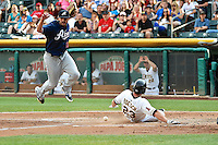 Mark Serrano (13) of the Reno Aces tries to cover home plate as Brennan Boesch (23) of the Salt Lake Bees slides in Pacific Coast League action at Smith's Ballpark on July 24, 2014 in Salt Lake City, Utah.  (Stephen Smith/Four Seam Images)