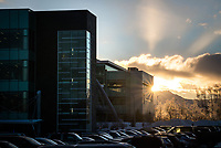 The sun rises behind UAA's Health Sciences Building and Engineering and Industry Building.