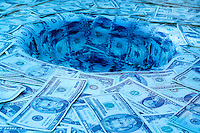 Swirling money as it goes down the drain
