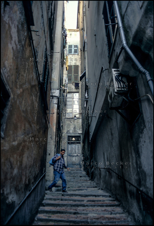 Genova, una persona in uno stretto vicolo tra vecchie case --- Genoa, a person in a narrow alley between shabby houses