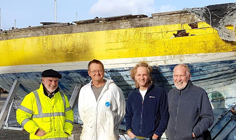 The DB21 Naneen arrives in Kilrush in 2016 pre-restoration, with (left to right) Fionan de Barra, boatbuilder Steve Morris, designer Paul Spooner, and Hal Sisk.