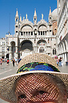 Venice Italy 2009. Woman tourist wearing straw hat St Marks Square.  Piazza San Marco. Basilica San Marco in background.<br /> Venice is like a crumbling open air museum and sinking under the weight of 20 million visitors a year. Only 30% of Venice's visitors stay overnight the rest stay out of town or on their cruise ships.