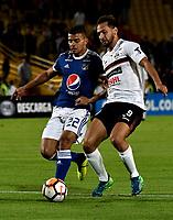 BOGOTÁ - COLOMBIA, 15-08-2018: Jhon Duque (Izq.) jugador de Millonarios (COL), disputa el balón con Julio Santa Cruz (Der.) jugador de General Díaz (PAR), durante partido de vuelta entre Millonarios (COL) y General Díaz (PAR), de la segunda fase por la Copa Conmebol Sudamericana 2018, en el estadio Nemesio Camacho El Campin, de la ciudad de Bogotá. / Jhon Duque (L) player of Millonarios (COL), fights for the ball with Julio Santa Cruz (R) player of General Diaz (PAR), during a match of the second leg between Millonarios (COL) and General Diaz (PAR), of the second phase for the Conmebol Sudamericana Cup 2018 in the Nemesio Camacho El Campin stadium in Bogota city. VizzorImage / Luis Ramirez / Staff.