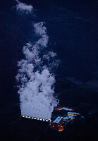 aerial photograph of one of the Geysers geothermal power plants at night.  The geothermal power plants at the Geysers, most of which are owned by Calpine are, the largest group of geothermal power plants in the world, Lake County, California.