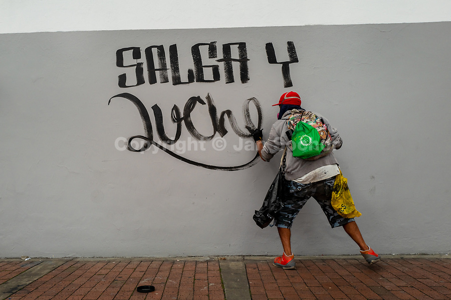 A radical student of the Universidad Nacional de Colombia paints a political slogan on the wall during a protest march against government's policies and corruption within the public educational system in Bogotá, Colombia, 24 October 2019.
