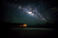 The Milky Way dominates a starry sky over Shipwreck's (or Shipwreck) Beach in Po'ipu, Kaua'i. The beach is connected with Maha'ulepu Heritage Trail.