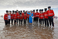 Pictured: A man dressed as The Queen followed by Royal Guards. Wednesday 25 December 2019<br /> Re: Hundreds of people in fancy dress, have taken part in this year's Porthcawl Christmas Swim in south Wales, UK.