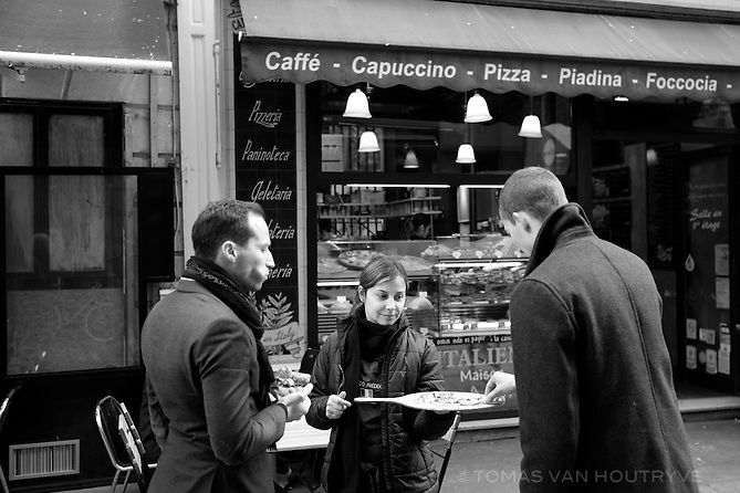 A server from an Italian restaurant offers pizza samples to passerby on rue Montorgueil in Paris, France three days after coordinated terrorist attacks struck the heart of the French capital. A majority of restaurants and businesses showed resilience in the aftermath of the attacks.