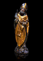 Gothic wooden statue of Sant Nicolau (Nicholas) from Gremany, circa 1500, tempera and gold leaf on wood, from the church of San Miguel de Medina del Campo, Valladolid..  National Museum of Catalan Art, Barcelona, Spain, inv no: MNAC  65507. Against a black background.