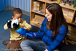 Educaton preschool 4-5 year olds play therapist working with boy in classroom using puppets horizontal