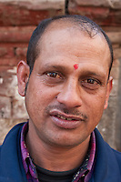 Kathmandu, Nepal.  A Nepali Vendor in the Durbar Square Market wears a tikka on his forehead, a red mark serving as a blessing and a symbol of Hinduism.