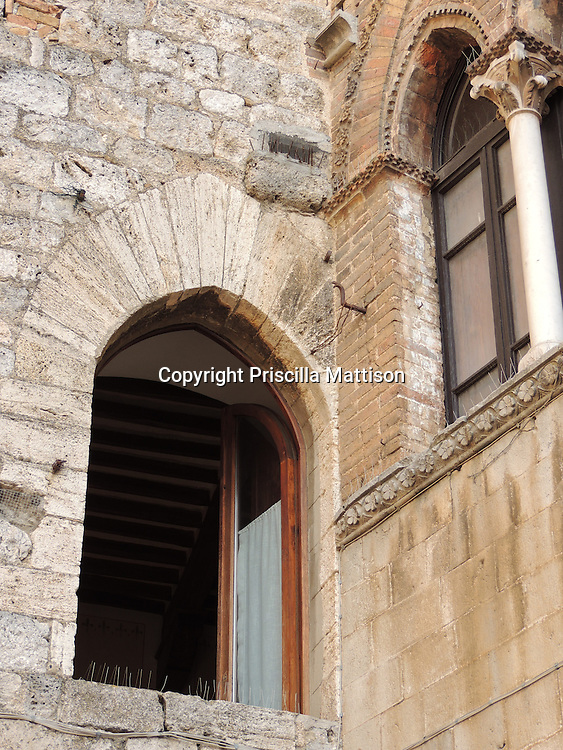 San Gimignano, Italy - October 4, 2012:  Two arched windows at right angles.