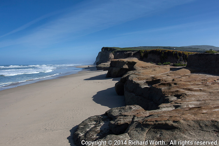 A couple strolls on the beach below the bluffs at Pomponia State Beach on the California coast south of Half Moon Bay.