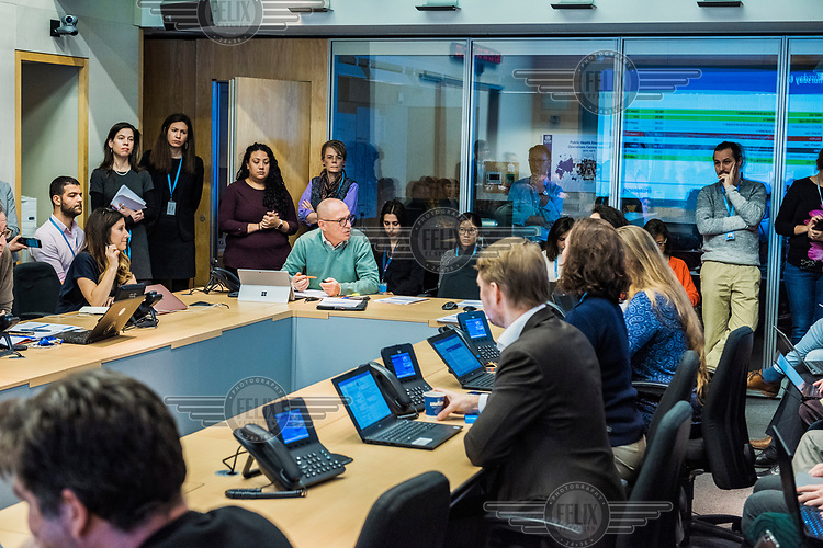 The daily, morning Acute Events Management meeting in the SHOC room (Strategic Health Operations Centre), at the World Health Organization (WHO) headquarters. The WHO, monitors global public health events around the clock, and facilitates international collaboration during public health emergencies and daily operations. The meeting is being led by Thomas Grein (in green sweater). Current emergency situations, including coronavrius and ebola, were discussed.
