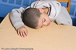 Educaton preschool 4-5 year olds boy sitting alone resting head on table horizontal sad or tired