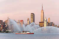 """WEEHAWKEN, NJ - JULY 4: FDNY fire boat Marine 9 """"Fire Fighter"""" puts on a water show on the Hudson river, with the Empire State Building and Manhattan skyline in the background, prior to the annual Macy's Fourth of July fireworks on Friday, July 4, 2009."""