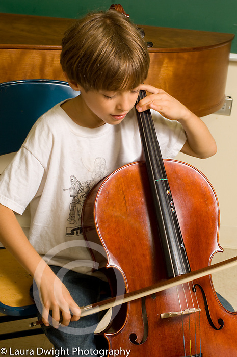 9 year old boy playing the cello at pubic elementary school with music enrichment