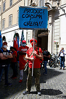 A man carries a banner with the words produce, consume and die, during the demonstration of the trade unions in Piazza Montecitorio .<br /> Rome (Italy), May 28th 2021<br /> Photo Samantha Zucchi Insidefoto