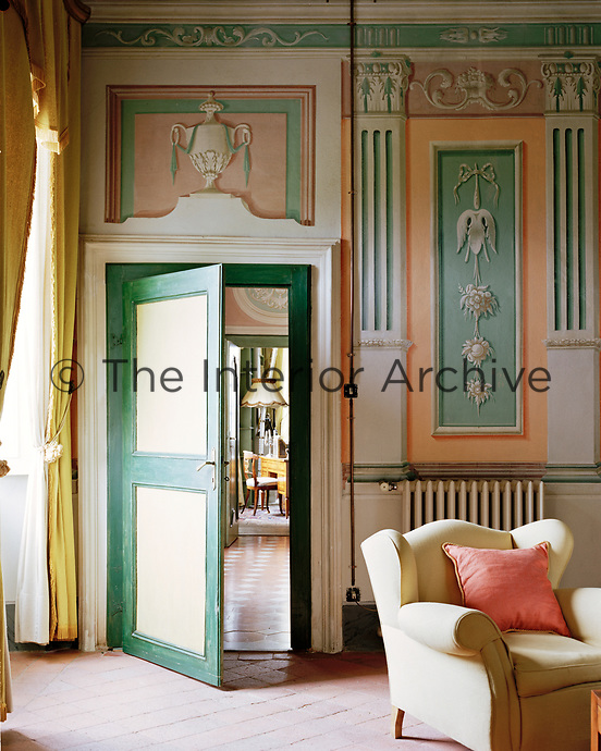 A corner of the vast living room, complete with neo-classical murals and lavish gold curtains. Cool terracotta floor tiles help with climate control.