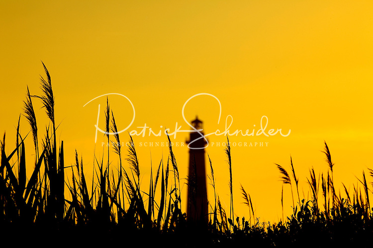 The popular Bodie Island Lighthouse at sunset on a clear summer day. Bodie Island Lighthouse, located on Bodie Island on North Carolina's Outer Banks, was built in 1872. It stands 156 feet tall and is located on the Roanoke Sound side of the first island that is part of the Cape Hatteras National Seashore. The lighthouse is just south of Nag's Head, a few miles before Oregon Inlet. The conical-shaped lighthouse has white and black bands with a black lantern house. Charlotte NC photographer Patrick Schneider has extensive photo collections of the following lighthouses: Bodie Island Lighthouse, Bald Head Island Lighthouse, Cape Fear Lighthouse, Cape Hatteras Lighthouse, Cape Lookout Lighthouse, Currituck Beach Lighthouse, Diamond Shoal Lighthouse, Federal Point Lighthouse, Oak Island Lighthouse, and Ocracoke Lighthouse on Ocracoke Island.