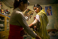 17 year old wrestler Alicia Flores (fighting name), Patricia Kaly (real name) has her injured arm wrapped up by her sister Marina Kaly in her room. Patricia is a Cholita, a wrestler of native Aymara descent. When Cholitas fight they wear traditional costume. .