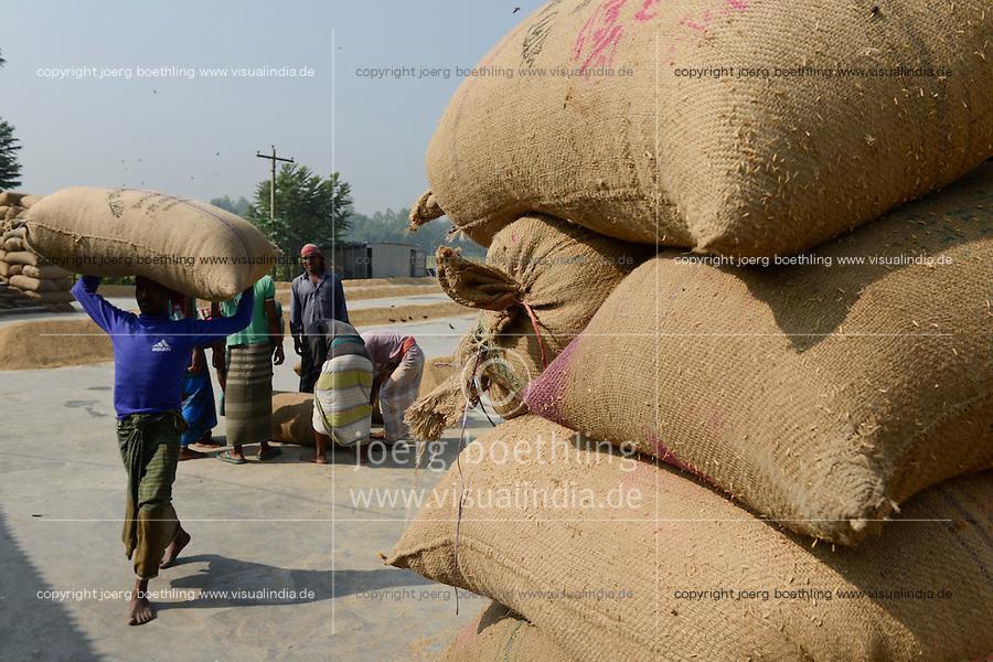 BANGLADESH Tangail, worker transport paddy in jute bags at rice mill near Kalihati / BANGLADESCH Arbeiter tragen Jutesaecke mit Reis in einer Reismuehle