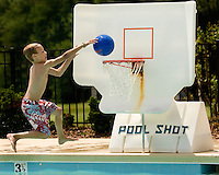 A boy jumps into a pool to shoot a basket at Rolling Hills Country Club in Monroe, NC.