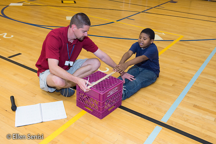 MR / Schenectady, NY. Zoller Elementary School (urban public school). Kindergarten inclusion classroom. Gym teacher helps student hold his knees down as student uses teacher-made equipment to test student flexibility. This is part of his students' yearly assessment of their physical education skills. MR: Mel16, Was3. ID: AM-gKw. © Ellen B. Senisi.