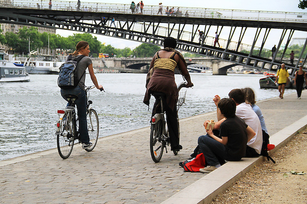 Family having lunch as bikers pass along the Seine River, Paris, France.
