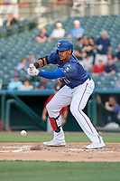Frisco RoughRiders Ronald Guzman (11) bunts during a Texas League game against the Springfield Cardinals on May 6, 2019 at Dr Pepper Ballpark in Frisco, Texas.  (Mike Augustin/Four Seam Images)